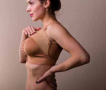 Young woman wearing a compressing bra after a breast augmentation surgery